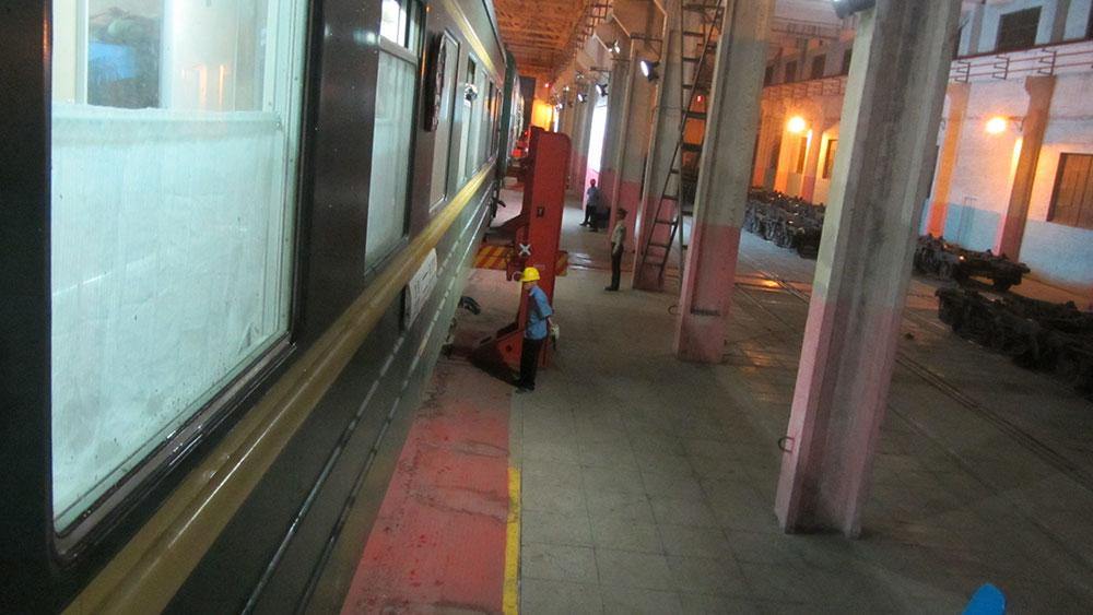 El tren transmongoliano suspendido en el aire mientras los operarios cambian las ruedas del vagón.